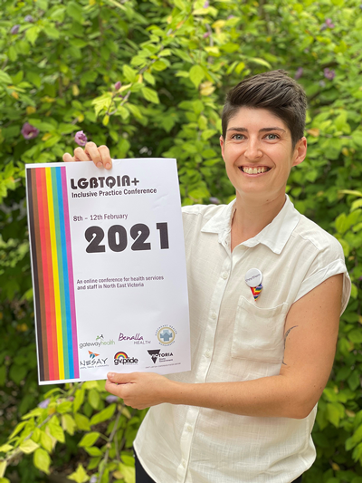 Allison Winters holding the LGBTQIA+ Inclusive Practice Conference 2021 poster