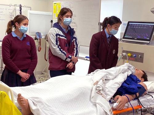 students from Galen College gather around a patient manikin