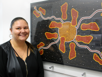 photo of Anita Cooper next to Aboriginal artwork