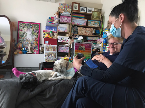 NHW nurse sat with patient, Betty, in her home holding a mobile device.