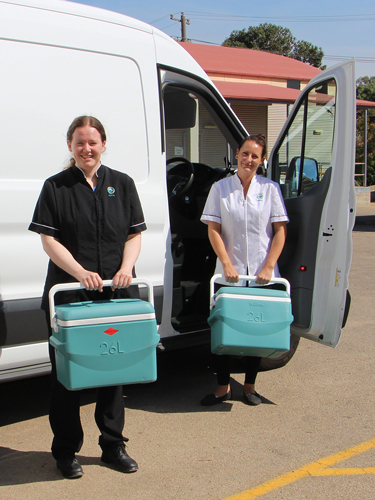 Dr Emily Pegan, Dentist and Tahlia Davis, Dental Assistant standing in front of a van holding onto food eskies about to start their Meals on Wheels run.