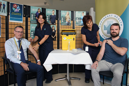 CEO Tim Griffiths and Board Chair Jonathan Green sat down having their flu shot by two Infection Prevention & Control nurses.