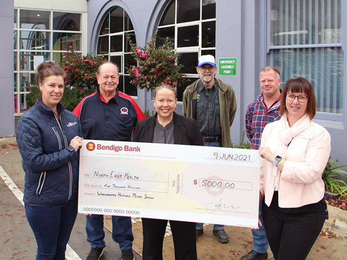 event organisers (from left) Ken Essenhigh, Lou Harper, Tania Cassidy (Bendigo Bank), Mick Daws, NHW Interim Chief Executive Officer Fiona Shanks and Richie Gardner holding a extra large display cheque for the value of $5000