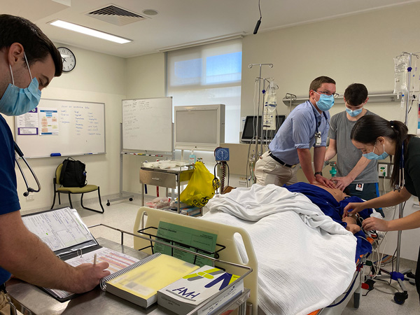 Three medical students practising on CPR on a manikin in a hospital environment with a four student taking notes.