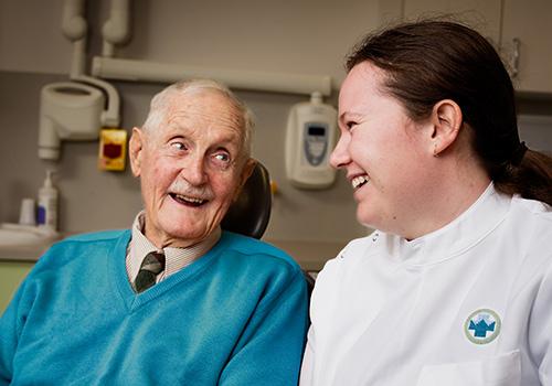 NHW female dentist and elderly gentleman