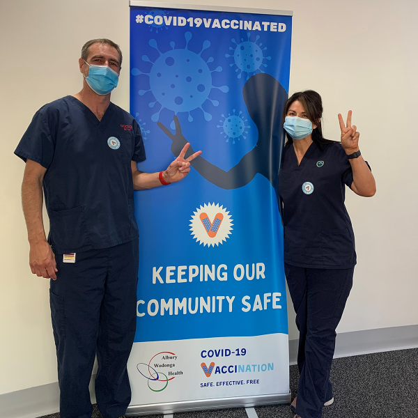 Frontline medical workers stood in front of COVID vaccine campaign poster