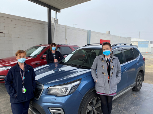 Three female NHW staff wearing mask and stood next to car where the new screening clinic will be located.
