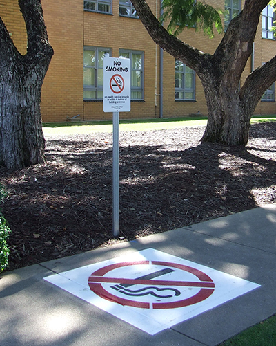 no smoking signs on the painted on pavement outside NHW marking the smokefree zone