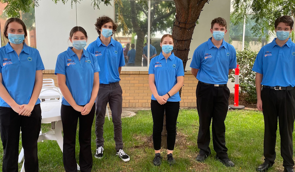 A group of young six students wearing masks