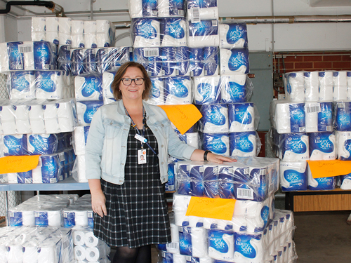 NHW Volunteer Coordinator, Lee O'Neill standing in front of a huge stack of thousands of toilet rolls