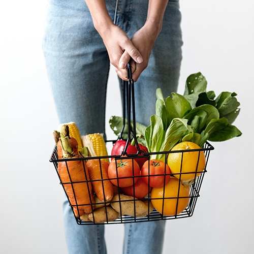 woman carrying basket of fruit and veg